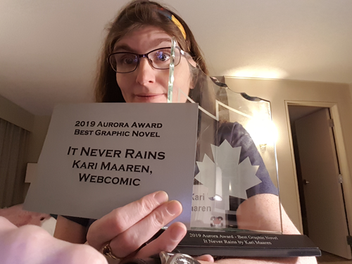 "Kari, a middle-aged white woman with long brown hair, holds an Aurora Award trophy, which looks a bit like a curved sheet of ice with a jagged top and a maple leaf printed on it, as well as a silver card reading, ""2019 Aurora Award / Best Graphic Novel / It Never Rains / Kari Maaren, / Webcomic."""